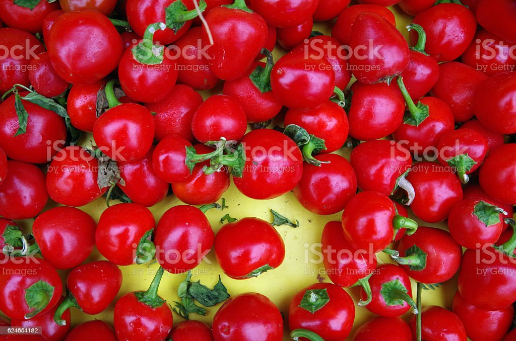 Red cherry peppers on yellow background stock photo