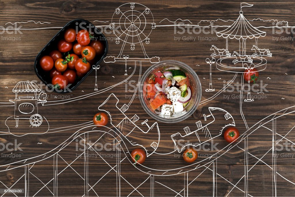 Red cherry tomatoes lying near bowl with greek salad royalty-free stock photo