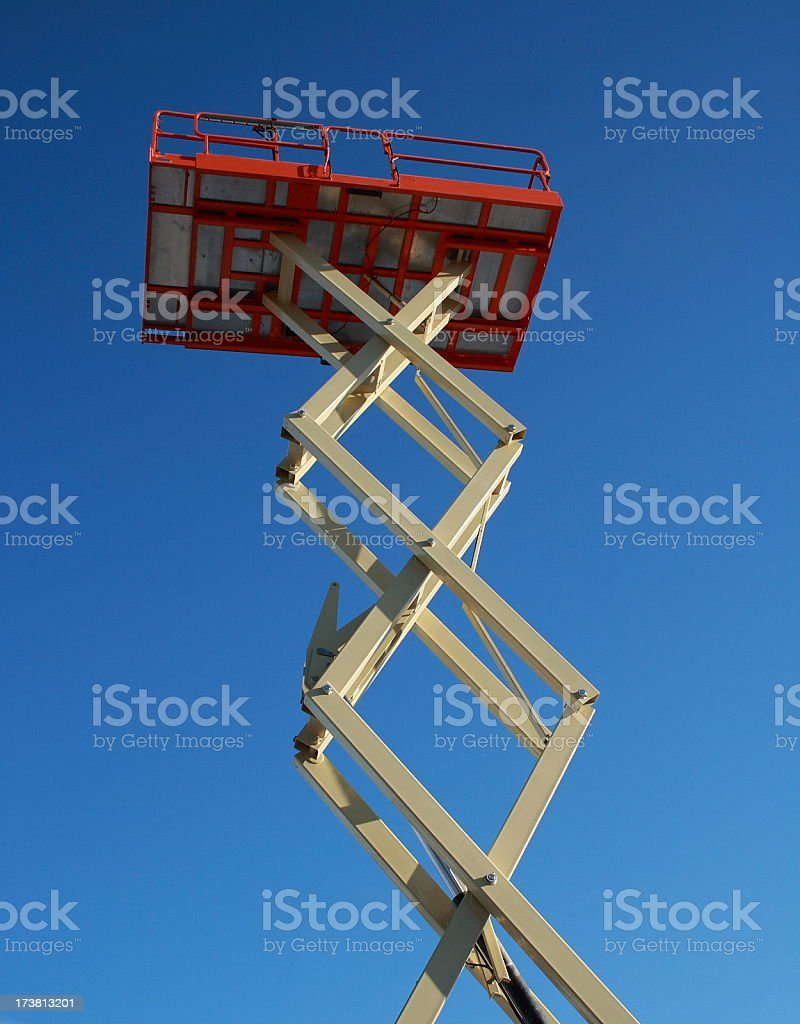 Red cherry-picker platform extended into the blue sky royalty-free stock photo