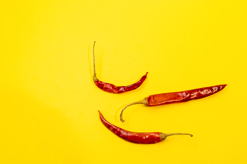 Red Chile de árbol chilis layed out as pattern on fun vibrant yellow