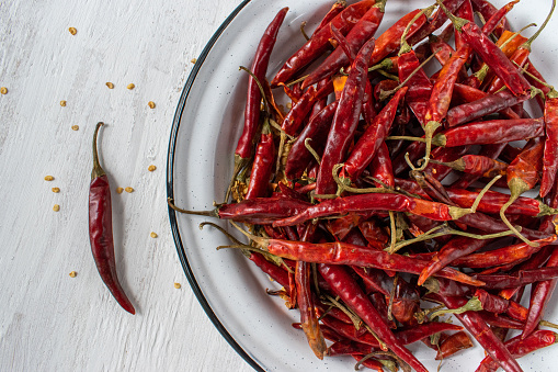 Red Chile de árbol chilis on rustic white background