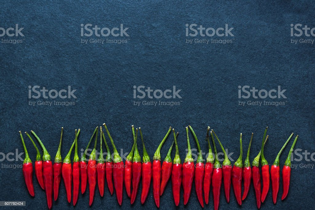 Red chili hot peppers on black slate stock photo
