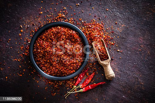 Spices: Top view of a black bowl filled with red chili pepper flakes shot on abstract brown rustic table. A wooden serving scoop with pepper flakes is beside the bowl, pepper flakes are scattered on the table. Three dried red chili peppers are beside the bowl. Predominant colors are brown and red. Low key DSRL studio photo taken with Canon EOS 5D Mk II and Canon EF 100mm f/2.8L Macro IS USM.