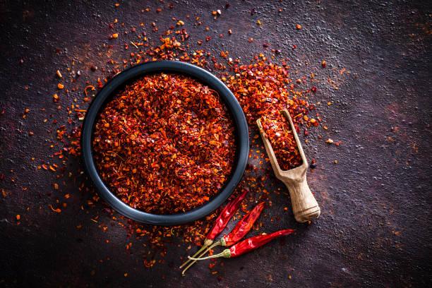 rode chili peper vlokken geschoten van boven - paprikapoeder stockfoto's en -beelden