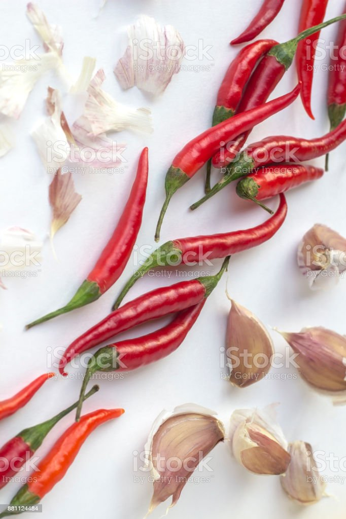Red chili peppers and garlic cloves on a white background diagonally. Top view. Vertically stock photo