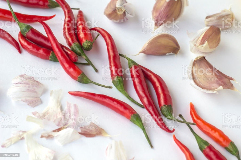 Red chili peppers and garlic cloves on a white background diagonally. Top view. Horizontally stock photo