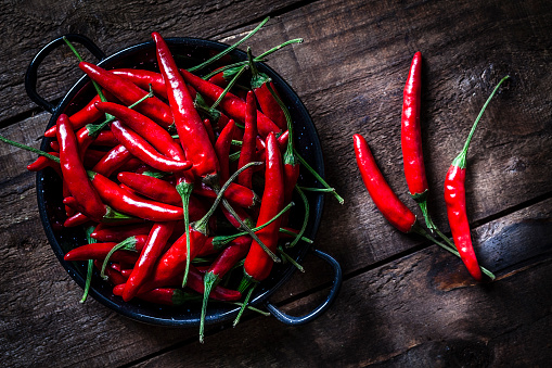 Red chili peppers shot from above on rustic wooden table. A chili peppers heap is in a small pan and three chili peppers are out placed directly on the table. Predominant colors are red and brown. Low key DSRL studio photo taken with Canon EOS 5D Mk II and Canon EF 100mm f/2.8L Macro IS USM