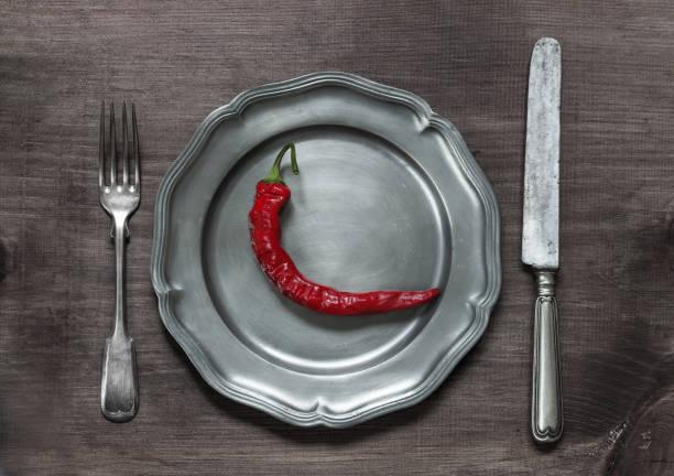 rote chilischote auf zinnteller - peperoni stiche stock-fotos und bilder