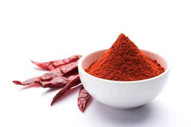red chilli powder in a bowl with dried red chillies over colourful background or pile of red chilli powder over plain background - pepper seasoning stock photos and pictures