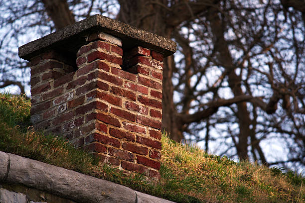 red kamin auf gras-cheminee rouge sur herbe - hobbit häuser stock-fotos und bilder