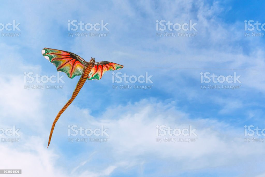A red chinese kite with dragon head flying in the wind - Royalty-free Activity Stock Photo
