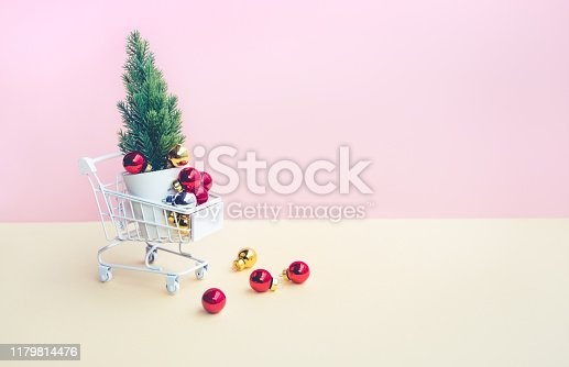 Red christmas ball and ornament on cart,trolley on pastel color background.Celebration festival and online shopping delivery concepts idea.Minimal design