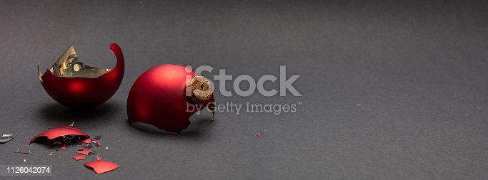 Christmas accident. Red Christmas ball broken, dark gray background, banner, copy space