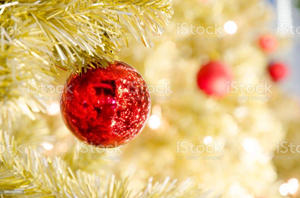 Red Christmas ball hanging on Gold Christmas Tree stock photo