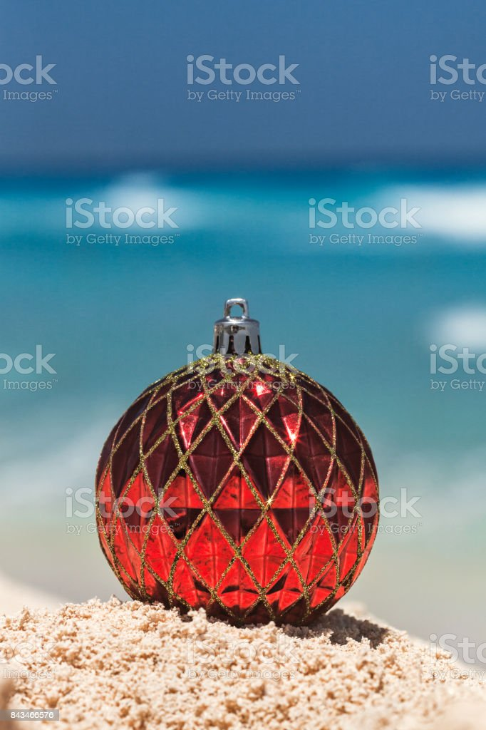Red Christmas ball on yellow sand at tropical beach, holiday concept stock photo