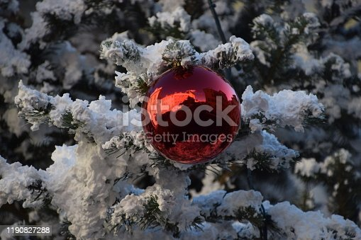 858960516 istock photo Red Christmas ball ornament on tree with fake snow detail 1190827288