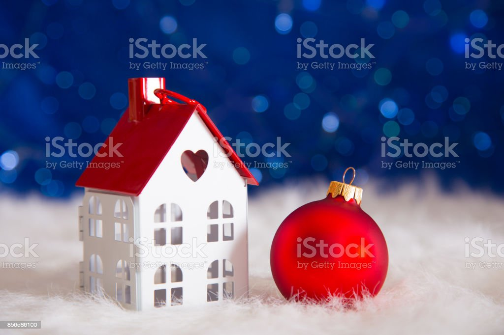 Red Christmas.Red Christmas Ball With Toy Little House On White Fur With Garland Lights On Blue Bokeh Background Stock Photo Download Image Now
