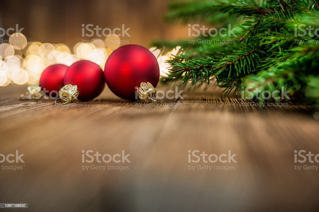 Red Christmas balls and fir twigs on rustic wood and sparkles light backgorund stock photo