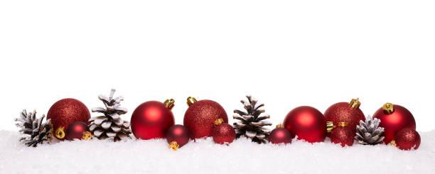 Bolas de Natal vermelhas e pinhas isoladas na neve - foto de acervo