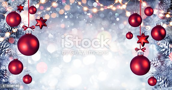 istock Red Christmas Balls Hanging With Snowy Fir branches And String Lights 873598186