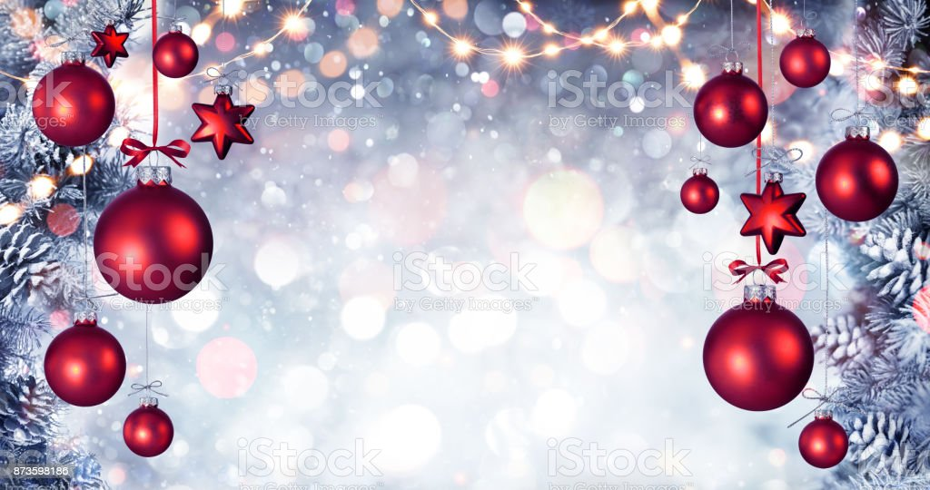Red Christmas Balls Hanging With Snowy Fir branches And String Lights stock photo