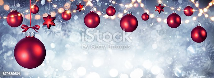 istock Red Christmas Balls Hanging With String Lights 872635604