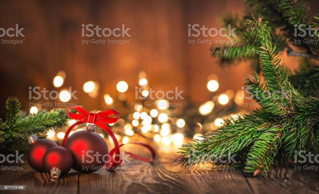 Rote Weihnachtskugeln auf altem Holz mit Weihnachtsbeleuchtung – Foto