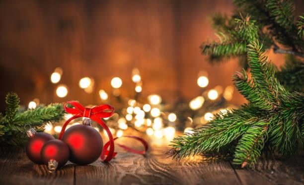 rote weihnachtskugeln auf altem holz mit weihnachtsbeleuchtung - holzdeko weihnachten stock-fotos und bilder