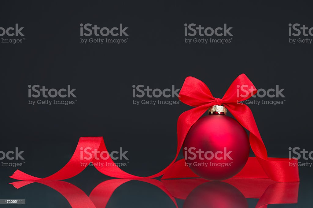 red christmas bauble and ribbon on dark background stock photo