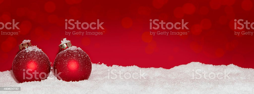 red Christmas baubles in the snow stock photo