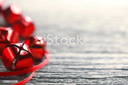 A random grouping of red Christmas jingle bells resting on a rustic wood surface. Photographed with a very shallow depth of field.