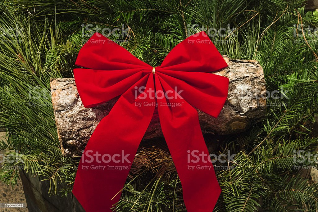 red Christmas bow on log with evergreen garland stock photo