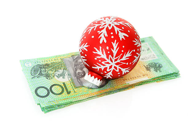 Red Christmas bulb ornament resting on stack of money stock photo