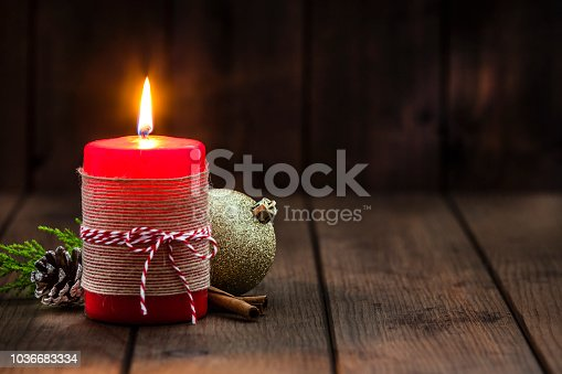 Red Christmas candle with Christmas decoration on rustic wood table. The candle is at the left of an horizontal frame. Predominant colors are brown, yellow and red. DSRL studio photo taken with Canon EOS 5D Mk II and Canon EF 70-200mm f/2.8L IS II USM Telephoto Zoom Lens