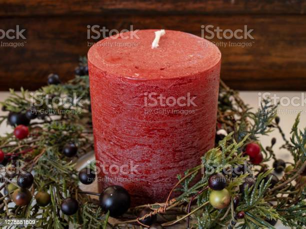 Photo of A red Christmas candle surrounded by cedar boughs and berries