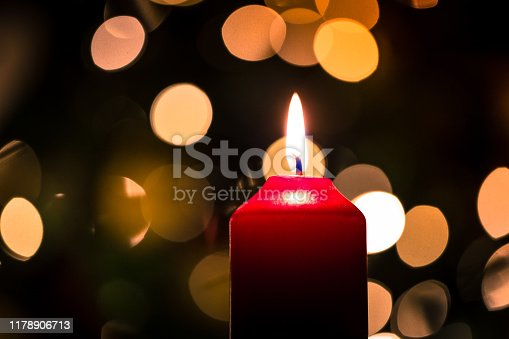 Close up color image depicting a lit red wax candle in the home at Christmas, surrounded by glowing Christmas lights (rendered into attractive bokeh circles) in the background. Room for copy space.