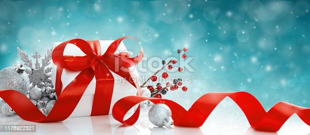 Red Christmas gift box and baubles on blue background. Holiday greeting card