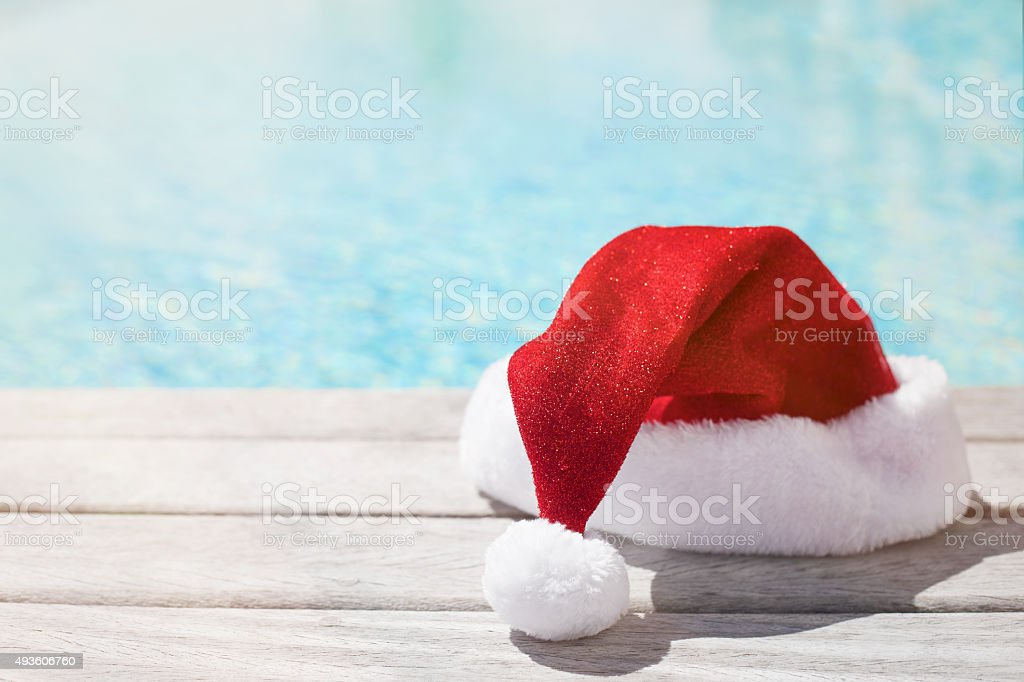 Red Christmas hat sitting by the pool stock photo