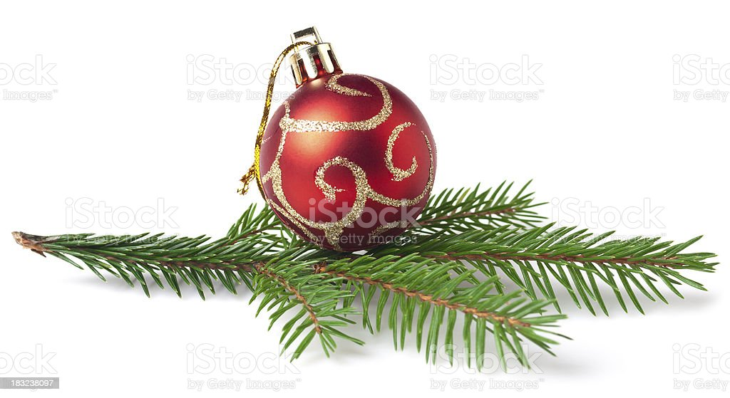 Red Christmas ornament with gold swirls atop a pine branch royalty-free stock photo