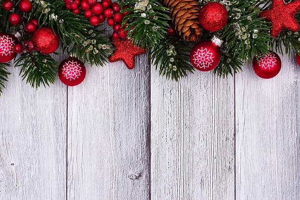 Red Christmas Ornaments And Branches Top Border On White Wood Stock Photo
