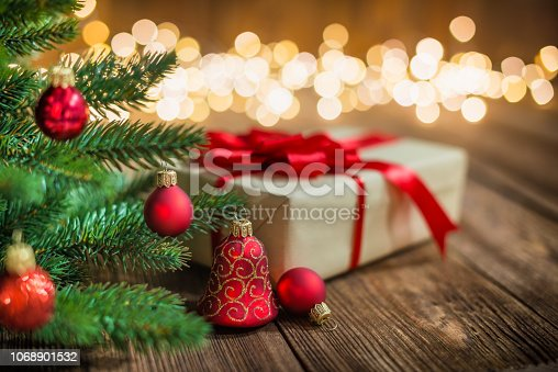 Red Christmas tree decorated with Ornaments and Gift on Wood Background with defocused lights sparkles