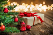 istock Red Christmas Ornaments and Gift on Wood Background with defocused lights sparkles 1068901532
