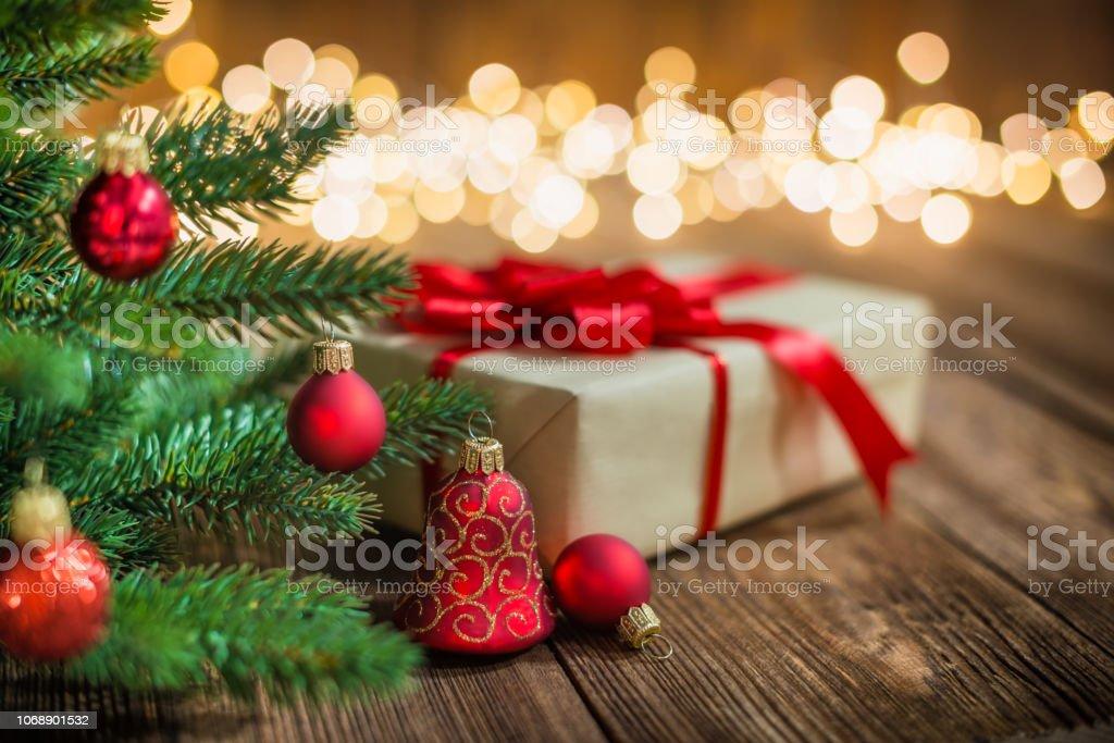 Red Christmas Ornaments und Geschenk auf Holz Hintergrund mit defokussierten Lichtern funkelt – Foto