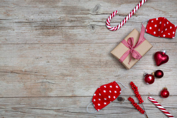 Red Christmas ornaments on wooden background, red bauble balls and a small present stock photo