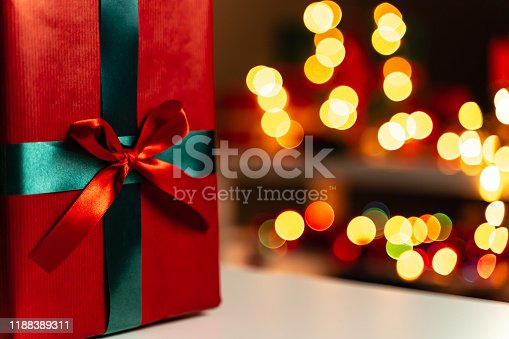 507751629 istock photo Red Christmas present close-up, defocused Christmas lights in background, bokeh 1188389311