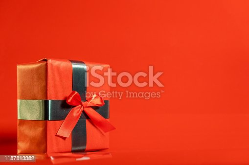 507751629 istock photo Red Christmas present on red background 1187813382