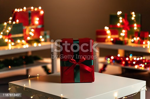 507751629 istock photo Red Christmas present on white table, defocused Christmas lights in background, bokeh 1187813451
