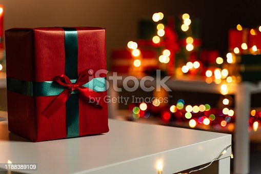 507751629 istock photo Red Christmas present on white table in front defocused Christmas lights in background, bokeh 1188389109