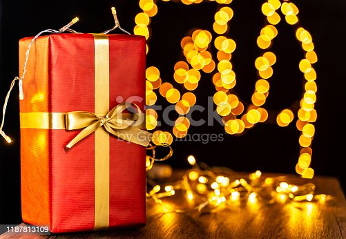 507751629 istock photo Red Christmas present with Christmas lights on it on wooden table, defocused Christmas lights in background, bokeh 1187813109