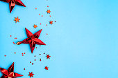 Red Christmas stars and snowflakes on blue background. Festive background with place for text. Holiday decor flat lay